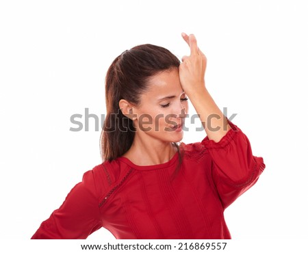 Portrait of positive young lady on red shirt with lucky sign and closed eyes standing on isolated studio