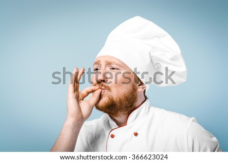 Portrait of positive young male chef in white uniform. Head-cook gesturing perfectly cooked food and standing against grey background - stock photo