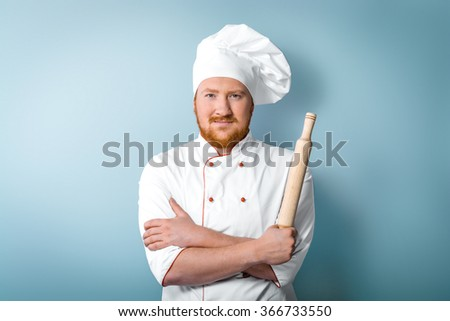 Portrait of positive young male chef in white uniform. Head-cook holding rolling-pin in one hand and looking at camera. Standing against grey background - stock photo