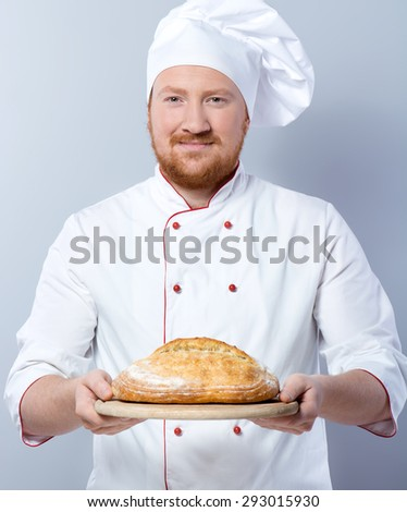 Portrait of positive young male chef in white uniform. Head-cook looking at camera and proposing freshly baked bread. Standing against grey background