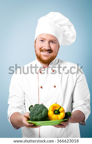 Portrait of positive young male chef in white uniform. Head-cook smiling, looking at camera and proposing fresh vegetables on plate. Standing against grey background - stock photo