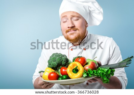 Portrait of positive young male chef in white uniform. Head-cook sniffing fresh vegetables on big plate. Standing against grey background - stock photo