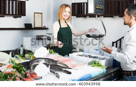 Portrait of positive young woman in fresh fish section of supermarket