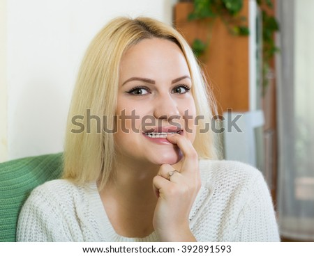 Portrait of positive young woman with finger over lips