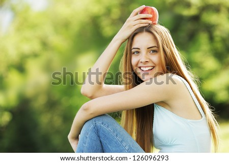 Portrait of positive young woman with red apple on her head
