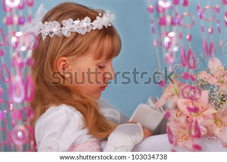 portrait of praying girl going to the first holy communion and posing in studio - stock photo