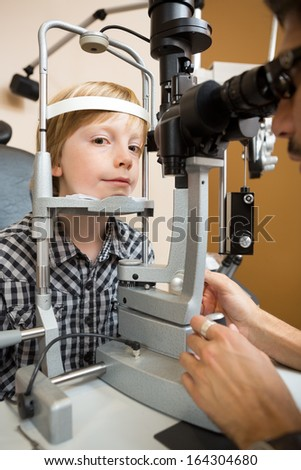 Portrait of preadolescent boy having his eyes tested with slit lamp by doctor - stock photo