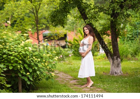 portrait of pregnant beautiful woman with hands over tummy in the park in summer - stock photo