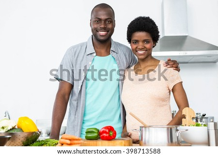 Portrait of pregnant couple embracing each other in kitchen at home