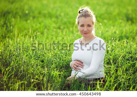 Portrait of pregnant woman  in field at sunset,