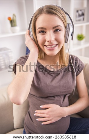 Portrait of pregnant woman is sitting on sofa at home and is listening music in headphones. - stock photo