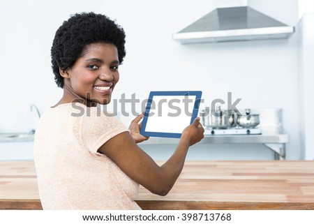 Portrait of pregnant woman using digital tablet in kitchen at home
