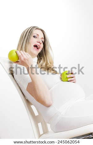 portrait of pregnant woman with green apples - stock photo