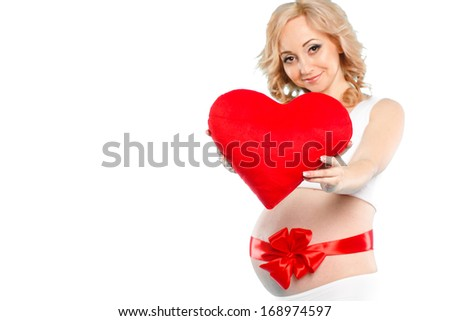 portrait of pregnant woman with tummy tied up by a red gift tape with red heart in her hands on white background. Studio portrait