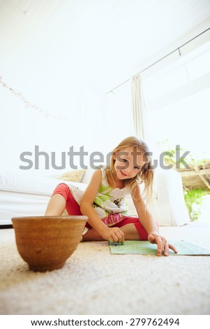 Portrait of preschool girl coloring picture on floor in her house. Young girl sitting on the floor painting a picture. - stock photo