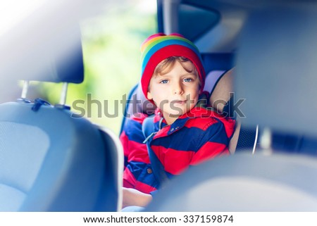 Portrait of preschool little kid boy sitting in car. Child in safety car seat with belt. Safe travel with kids and traffic laws concept. - stock photo