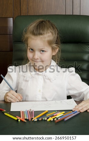 Portrait of preschooler girl drawing with pencils and thinking about it. Sitting in a green leather armchair, at the dark table