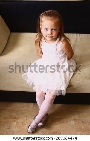 portrait of preteen small blond girl with long blond hair in white sleeveless dress sit on the sofa - stock photo