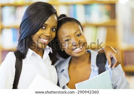 portrait of pretty african american college friends together in library - stock photo