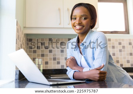 portrait of pretty african american woman with laptop in kitchen