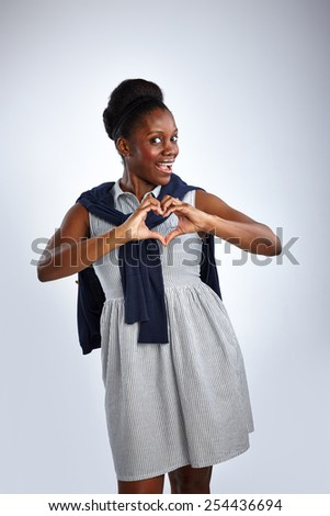 Portrait of pretty african woman making a heart shape with her hands against white background - stock photo