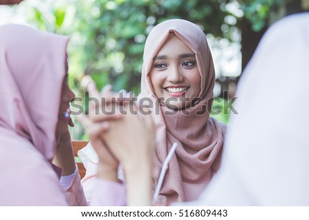 portrait of pretty asian muslim woman having fun in cafe together with friends