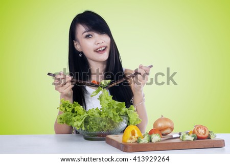 Portrait of pretty Asian woman smiling at the camera while holding two spoon to mix vegetables salad - stock photo