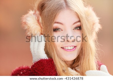 Portrait of pretty attractive fashionable woman in fall forest park. Gorgeous young girl in earmuffs. Autumn winter fashion. - stock photo