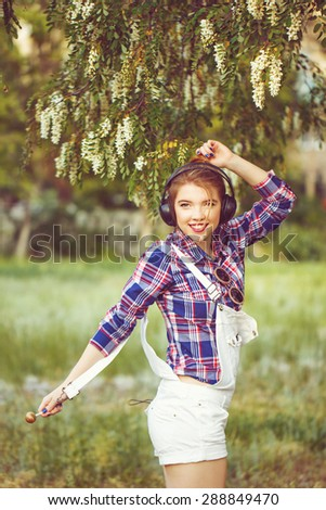 Portrait of pretty attractive girl hipster headphones. Girl dancing. Warm toning. The concept of happy life. - stock photo