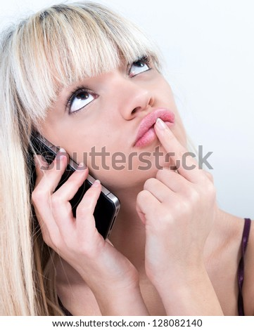 Portrait of pretty blond girl Portrait of pondering while phoning - stock photo