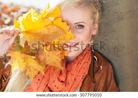 Portrait of pretty blonde girl in autumn park with maple leaves is wearing mint color sweater - stock photo