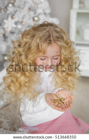 Portrait of pretty blonde little girl looks at a confetti at hands in Christmas studio