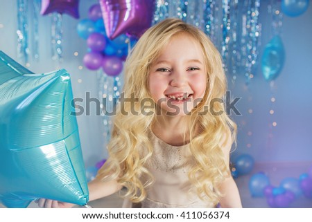 Portrait of Pretty blonde little girl with color balloons in a studio - stock photo