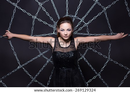 Portrait of pretty brunette posing at the web of chains - stock photo