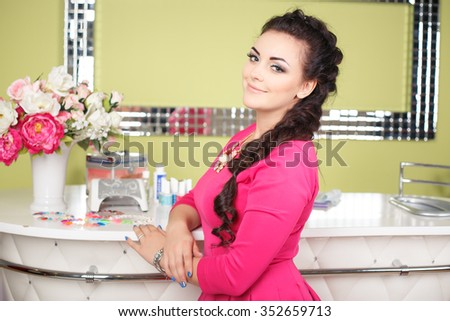 Portrait of pretty brunette young woman near nail bar. Customer in manicure salon