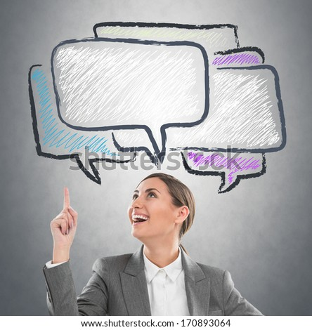 Portrait of pretty business woman looking at dialog symbols overhead - stock photo