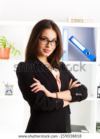 Portrait of pretty businessperson in eyeglasses posing in bureau. Young successful female sales manager at work.  - stock photo