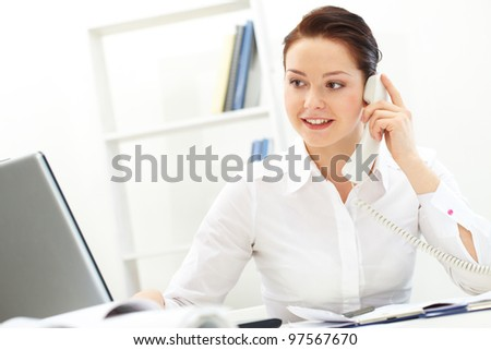 Portrait of pretty businesswoman calling in office - stock photo