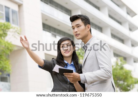 Portrait of pretty businesswoman explaining way to young man - stock photo