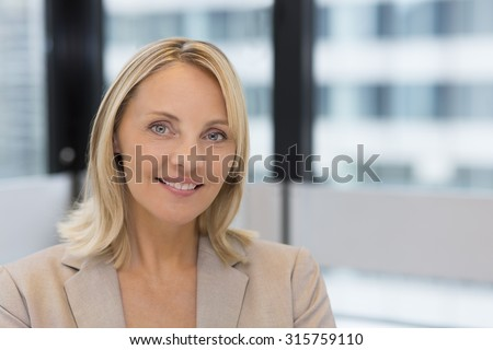 Portrait of pretty businesswoman in modern office. Building background - stock photo