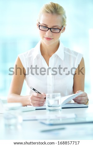 Portrait of pretty businesswoman making notes