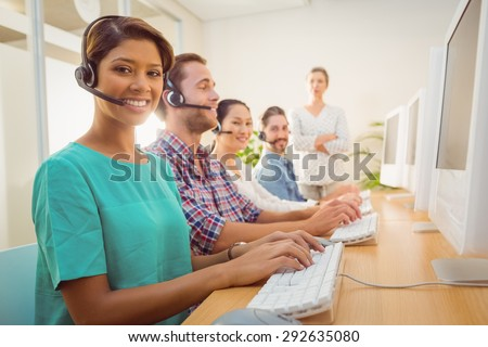 Portrait of pretty call center agent working under a manager supervision - stock photo