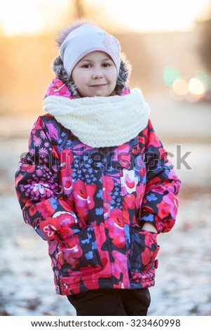 Portrait of pretty Caucasian girl standing in winter clothes with scarf and hat - stock photo
