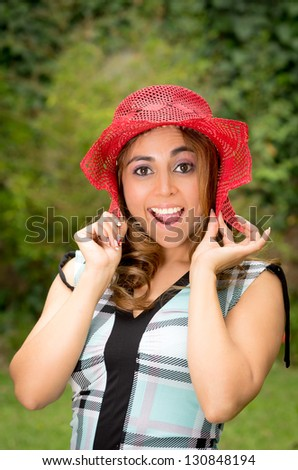 Portrait of pretty cheerful woman wearing dress and straw hat in sunny warm weather day. Walking at summer park and smiling - stock photo