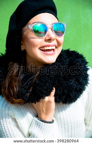 Portrait of pretty cheerful woman wearing white dress and black vintage hat in sunny warm weather day. Outdoor close up  of an attractive cheerful smiling woman on vacation at green urban wall. Spring - stock photo