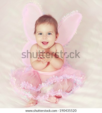 Portrait of pretty child girl in butterfly costume on pink - stock photo