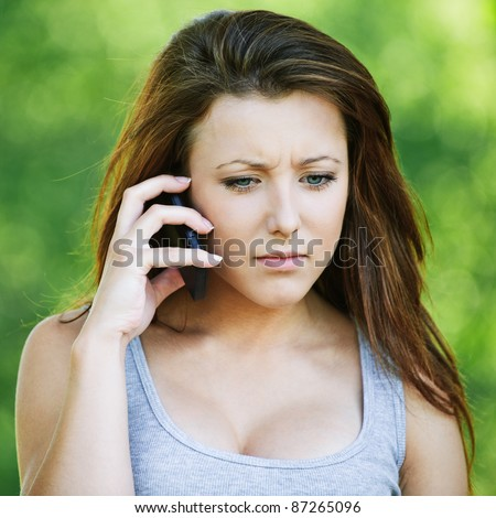 Portrait of pretty dark-haired serious girl speaking on mobile phone at summer green park. - stock photo