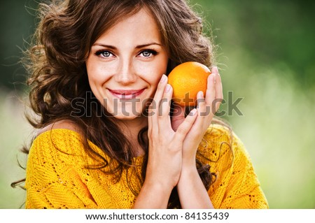 Portrait of pretty dark-haired woman holding juicy delicious orange at summer green park. - stock photo