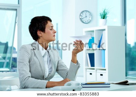 Portrait of pretty employer at workplace holding paper plane and looking at it - stock photo