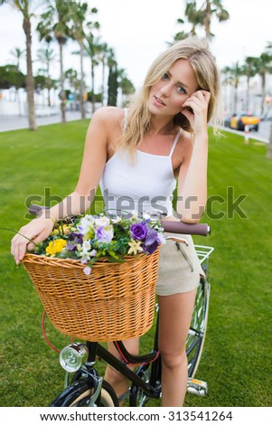Portrait of pretty face young woman standing in the park with her classic bicycle and looks at the camera, gorgeous woman enjoying holidays strolling on bike with basket of beautiful summer flowers - stock photo